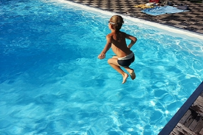 Child jumping into solar heated swimming pool